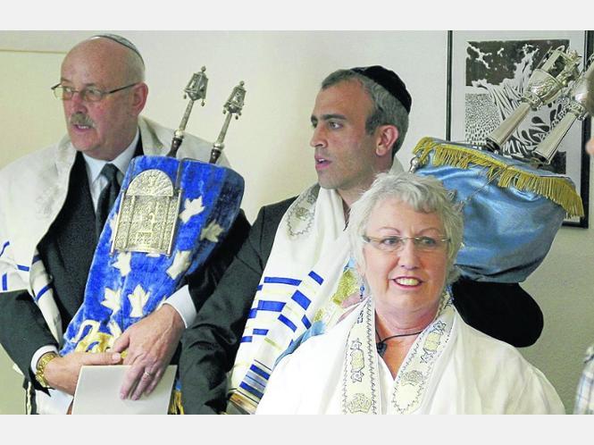 Zwei zusätzliche Torah-Rollen: Uwe Lengen (von links) und Gyu Kiewe tragen die Rollen. Eine ist eine Leihgabe des Fritzlarer Doms, die andere eine Geschenk aus Ohio. Vorne: Deborah Tal-Rüttger. Foto: Schaake
