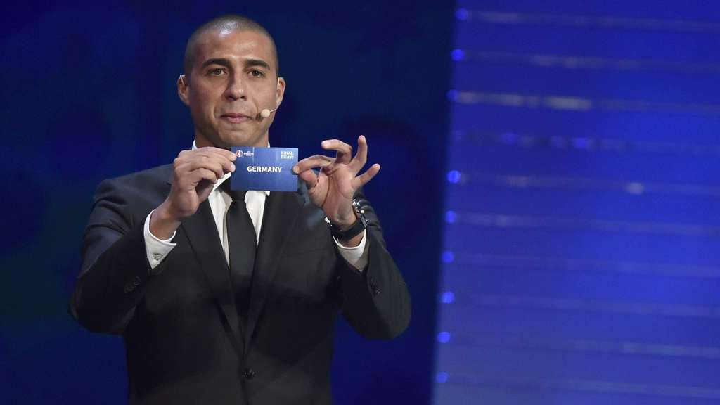 "Former French striker David Trezeguet shows the name of ""Germany"" during the final draw of the UEFA Euro 2016 football tournament in Paris on December 12, 2015. AFP PHOTO / LOIC VENANCE"