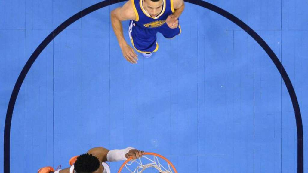 Warriors-Superstar Stephen Curry (r) kommt beim Dunking von OKC-Topscorer Russell Westbrook zu spät. Foto: Tyler Smith