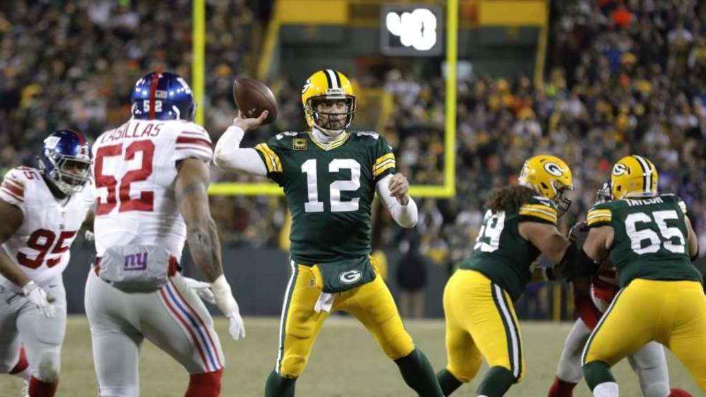 Packers-Quarterback Aaron Rodgers (M.) wirft einen Touchdown. Foto: Mike Roemer