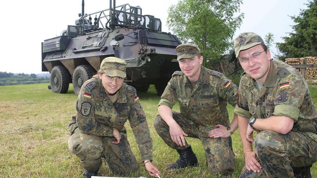 Hauptfeldwebel Franziska Ebell, Oberleutnant Christian Particke und Leutnant Christoph Böke während der Abschlussübung in Frankenau vor dem Transportpanzer Fuchs.