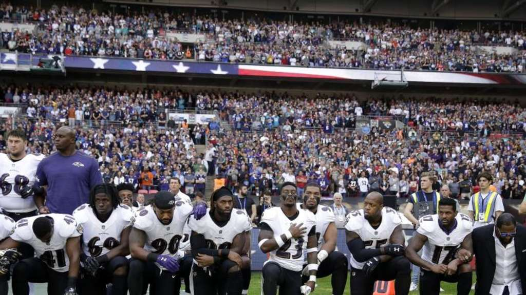 Spieler des Football-Teams Baltimore Ravens knien in London während der US-Nationalhymne aus Protest auf dem Rasen. Foto: Matt Dunham