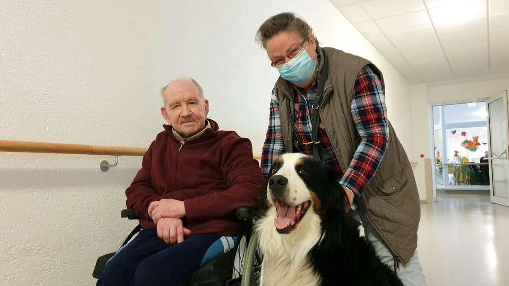 Ein alter Mann sitzt im Rollstuhl eine Frau mit Mund-Nasen-Schutz beugt sich zu ihm herunter, vor den beiden sitzt ein Berner Sennenhund.