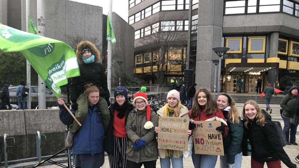 Eine Gruppe Jugendlicher steht mit Fahnen und Plakaten vor dem Neuen Rathaus in Göttingen